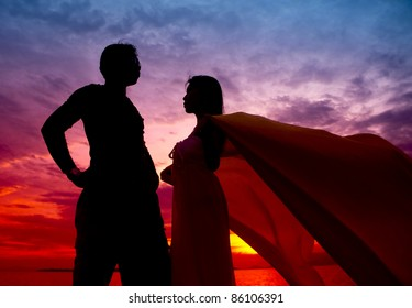Couple silhouette on the beach at sunset