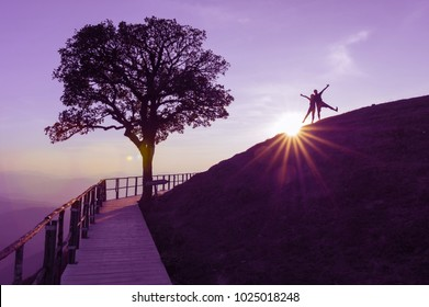 Couple silhouette on hill and lonely tree, The sun is falling down behind with lights flare On the top of Doi Pui Co,  Popular tourist attraction in Mae Hong Son, Thailand.