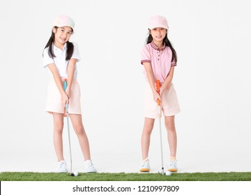 Couple of sisterhood Asian in sportswear and colorful hats are happy with pose the way they play golf on artificial glass, isolated on white background.