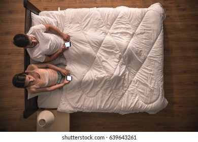 The couple sit on the bed and phone. view from above