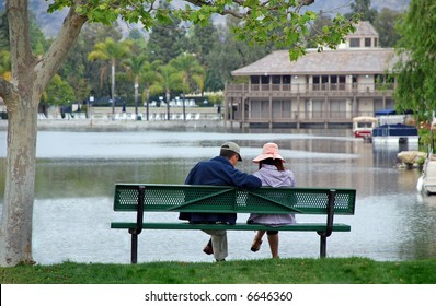 A couple sit on a bench by a lake, contemplating future plans.