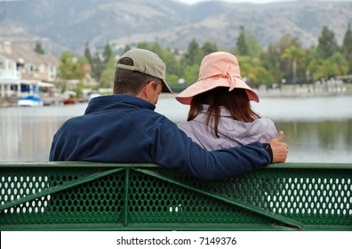 A couple sit on a bench by a lake, the man makes the thumbs up gesture.