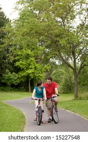 A couple, sit on bikes on a trail, staring at each other. vertically framed