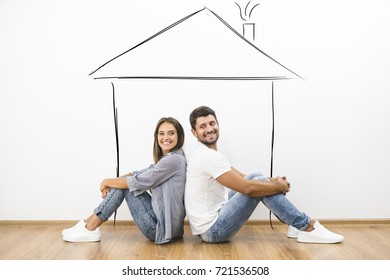 The couple sit on the floor near a house illustration on the wall