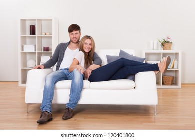 Couple sit on new couch bought at furniture shop.