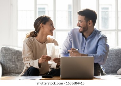 Couple sit on sofa busy with manage household budget, satisfied wife and husband using pc free online app for tracking spend of money, family individual entrepreneurs own business makes profit concept