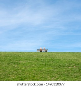 couple sit together on bench placed on top of grassy dike in friesland under blue sky