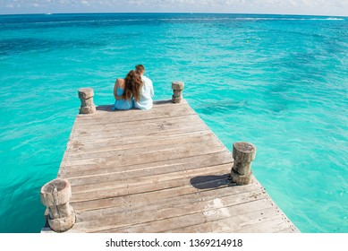 Couple siting at the wooden pier, hugging and looking at the turquoise water of caribbean sea in Cancun. Drone view picture.