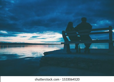 A couple sits on a bench and looks at the sea. A man and a woman on a date. Lovers drink wine on the beach at sunset. Bench on the pier.