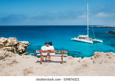 A couple sits on a bench and looks at the lagoon. Honeymoon lovers. Man and woman on the island. Couple in love on vacation. A voucher for a cruise trip. Sea tour. Honeymoon trip. Wedding travel