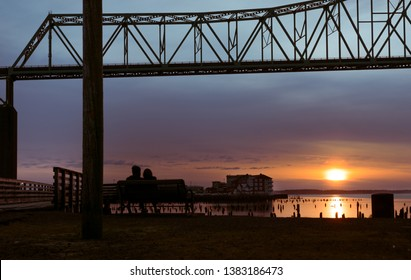 A couple sits on a park bench on the waterfront beneath the Astoria-Megler Bridge, silhouetted by the sunset. Astoria, Oregon