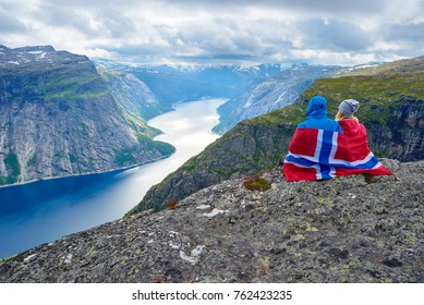 Couple sits on rock and looks at mountains near Trolltunga. Popular tourist attraction. Ringedalsvatnet - lake in the municipality of Odda in Hordaland county, Norway