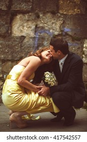 Couple sits squatting before old stone wall