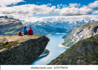 Couple sitting against amazing nature view on the way to Trolltunga. Location: Scandinavian Mountains, Norway, Stavanger. Artistic picture. Beauty world. The feeling of complete freedom
