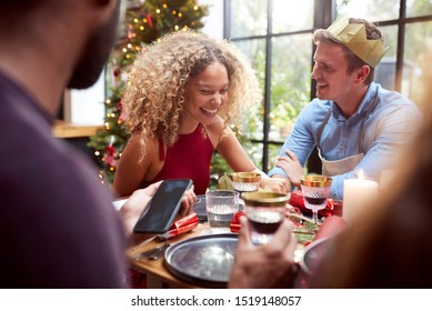 Couple Sitting Around Dining Table At Home For Christmas Dinner With Friends Talking