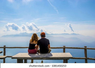 A couple sitting atop a bench table at the end of a hike overlooking Lago Maggiore, Ticino, Switzerland.
