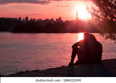 couple sitting back no face silhouettes and watching panoramic Kiev city sunset on the bank of the river Dnieper. Romantic pink view. Find a wife soulmate real estate for family in Ukraine concept