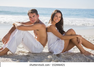 Couple sitting back to back on the sand at the beach