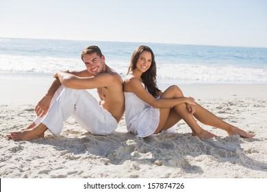 Couple sitting back to back on the sand smiling at camera at the beach