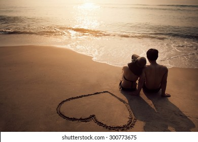 Couple sitting at the beach He was drawing a heart on the sand. During the summer