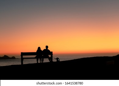 a couple sitting at a bench during sunset