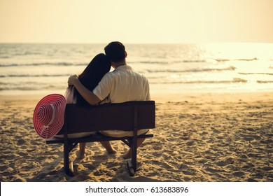 The couple is sitting by the beach in the evening, watching the sunset.