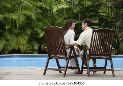 Couple sitting by swimming pool, looking at each other, rear view