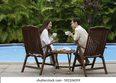 Couple sitting by swimming pool, have drinks, looking at each other
