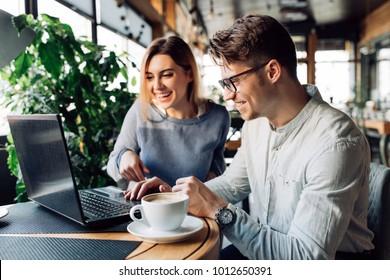 Ein Paar saß im Café und lachte fröhlich, schaute auf den Laptop-Bildschirm, verbringt Zeit mit Vergnügen, trinkt Kaffee.