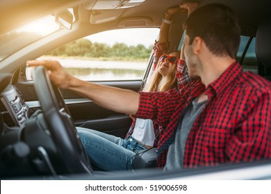 Couple sitting in the car listening to music and having fun. Enjoy a fun journey