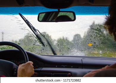 A couple sitting in the car while it is raining heavily. The windshield wipers have a lot to do and are busy to clear the window view to drive safely