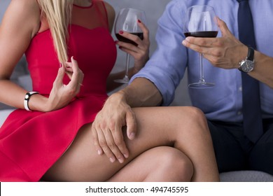 Couple sitting close each other with the man's hand on woman's tight