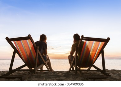 Couple sitting in deckchairs on paradise beach and thinking about perfect life
