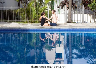 A couple sitting down by the pool, linking and crossing arms, stretching, smiling at each other - horizontally framed