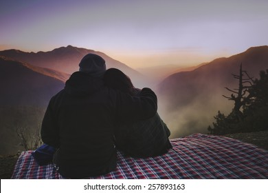 A couple is sitting at the edge of a mountain cliff enjoying the beautiful foggy view.