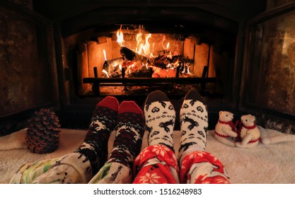 Couple sitting at the fireplace in the mountain chalet, relaxes by warm fire and warming up their feet . Female and male feet in woollen socks by the Christmas fireplace. Winter and holidays concept.