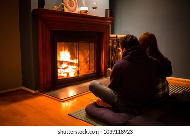 Couple sitting at fireplace with wine celebrating