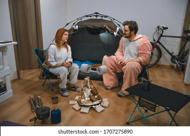 Couple sitting in folding chairs by the tent and bonfire. Camping in the apartment. Adventures at home, traveling around the room. quarantine entertainment Funny, fried marshmallows, toilet paper