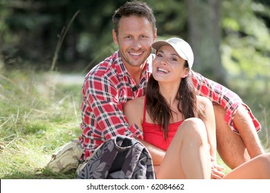 Couple sitting in forest on hiking day