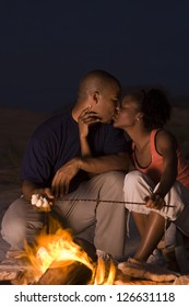 Couple sitting in front of campfire at night
