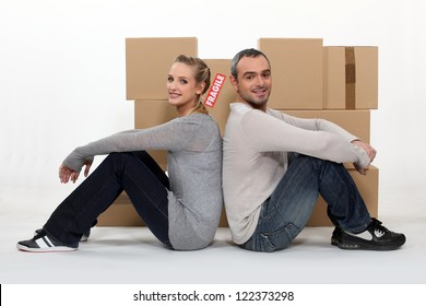 Couple sitting in front of cardboard boxes