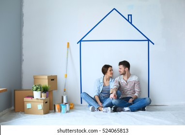 Couple sitting in front of painted home on wall