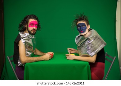 Couple sitting at the green table. Green background. Actors in the studio. Clowns. Futuristic makeup. Futuristic costumes.