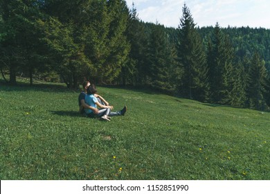couple sitting and hugging on green grass at forest
