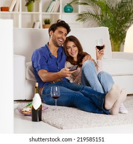 Couple sitting in the living room, having wine and watching TV.