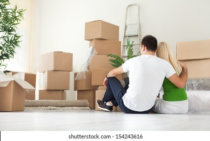 Couple sitting  and looking  lot of moving boxes, back view
