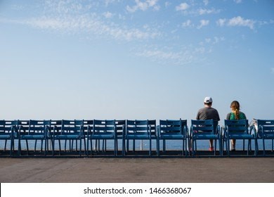 Couple sitting at Mediterranean Sea shore facing the beach