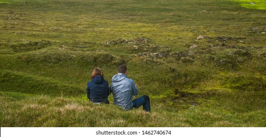 Couple sitting in the middle of the green moss field in the summer in Iceland ,Travel vacation and summer time concept.