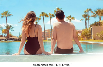 A couple is sitting near the pool, legs down in the water. A sunny day, a man and a girl enjoy the rest. Travel. Against the background of palm trees and houses. Couple at the hotel with a pool.
