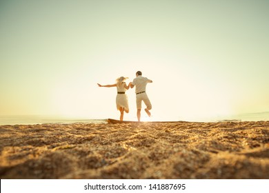 couple sitting on the beach at sunrise